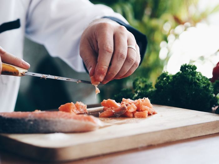 Master chef slice fresh salmon on chopping board. Cooking Japanese  Chef Chopping Close-up Cutting Board Day Food Food And Drink Freshness Healthy Eating Holding Human Hand Indoors  Lifestyles Men One Person People Preparation  Preparing Food Real People Salmon Salmon Sashimi