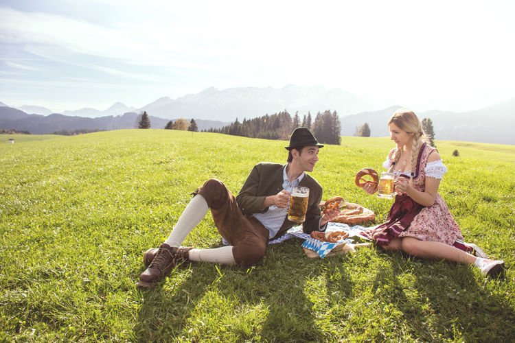 Couple in traditional german clothing drinking beer and eating pretzel surrounded by beautiful panorama in nature. Couple with beer and pretzel relaxing in nature. Couple Oktoberfest Bavaria Beer Dirdnl Germany🇩🇪 München Oktoberfest Traditional Clothing Bavarian Alps Bavarian Clothing Beer And Pretzel Beer Oktoberfest Couple In Tradional German Clothing Couple Oktoberfest Couple With Beer Couple With Beer And Pretz Dinking German Clothing Holding Mountain Oktoberfest 2018 Oktoberfest Beer People Oktoberfest Pretzel Relaxation Tradional Bavarian Clothing