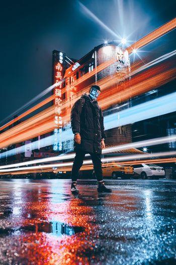 Blurred motion of man walking on illuminated bridge at night
