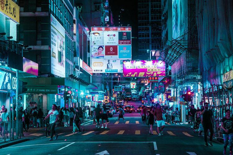 People walking on illuminated city street at night