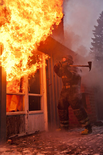 Man standing by fire on building