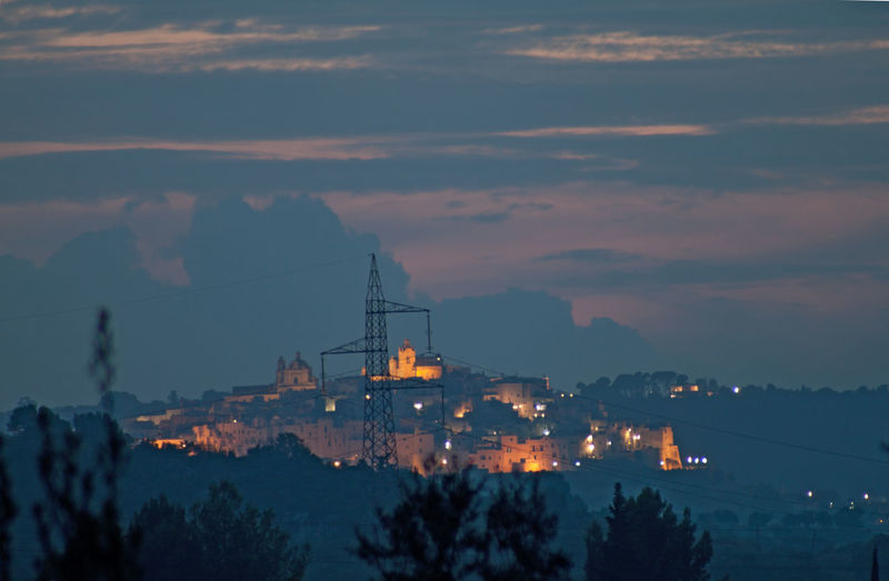 view of Ostuni by sunset Sunset Nightphotography Sky Silhouette Building Outdoors Illuminated Cityscape Electricity  Mountain Dramatic Sky Perspective Mediterranean  Ostuni No People Settlement Electricity Pylon Cloud - Sky Building Exterior Holiday Vacations Traveling