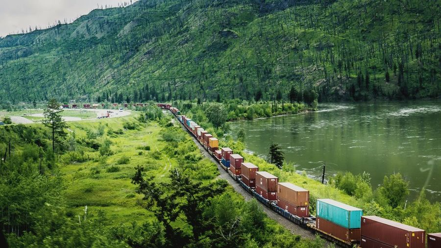 High angle view of freight train by lake against mountain