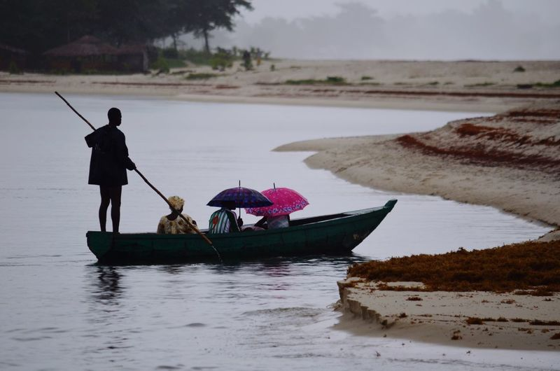 People In Boat At Lake On Rainy Day