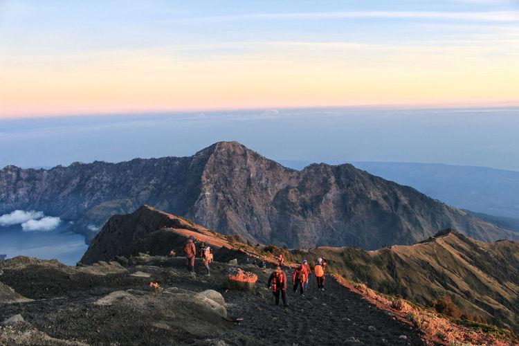 People On Mountain Peak During Sunset