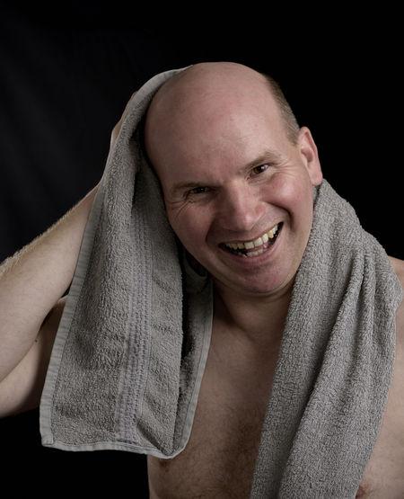 Portrait of smiling mid adult man against black background