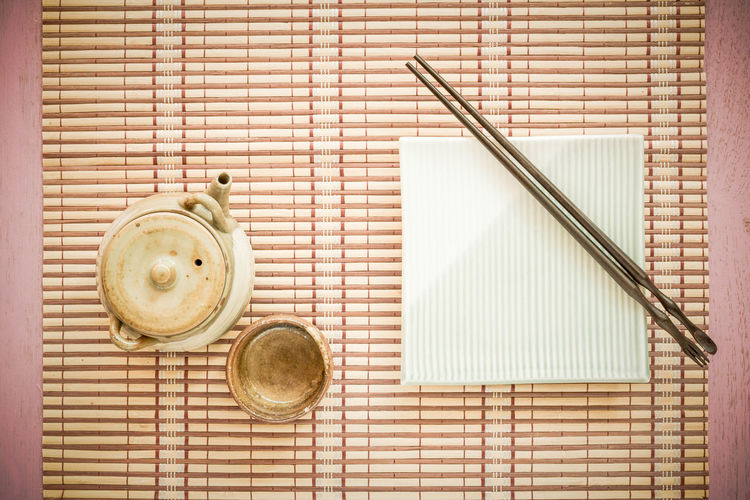 Directly above shot of teapot with chopsticks on bamboo placemat