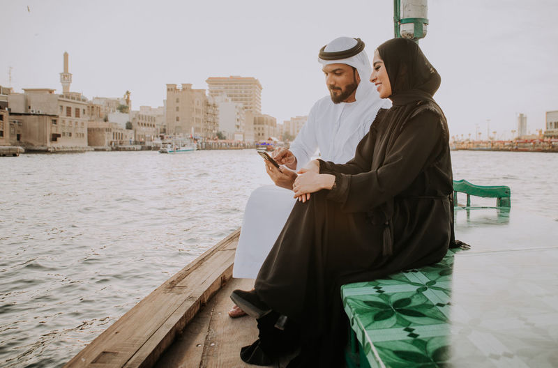 Couple using smart phone while sitting in boat on river during sunset