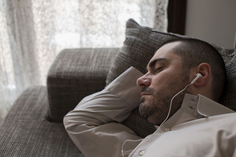 Close-Up Of Man Listening Music While Lying Sofa Sitting At Home