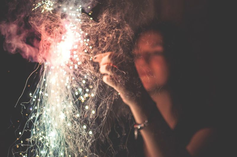Close-up of woman's hand with firecrackers at night