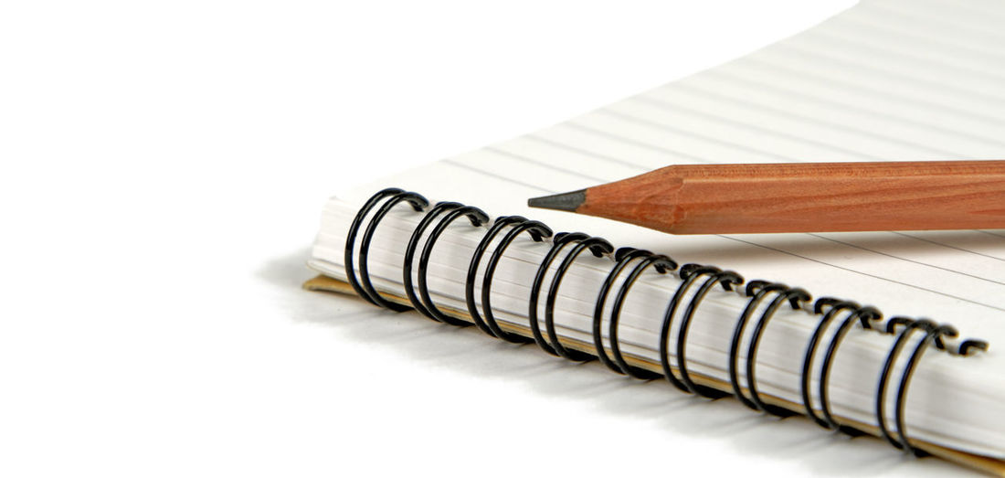 Office still life with a crayon on spiral notebook isolated over white background Paper Spiral Notebook White Background Close-up Office Business White Color Studio Shot Copy Space Education No People Pen Note Pad Writing Page Pencil Crayon