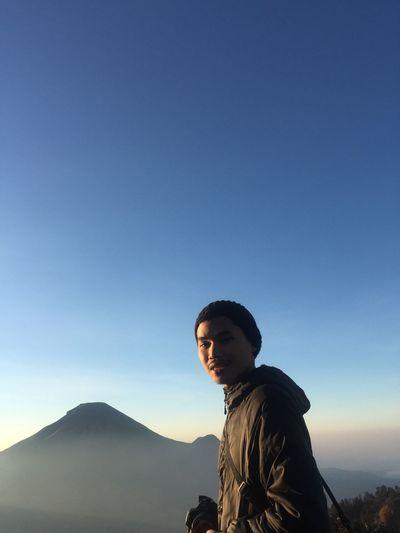 Portrait of man standing against blue sky