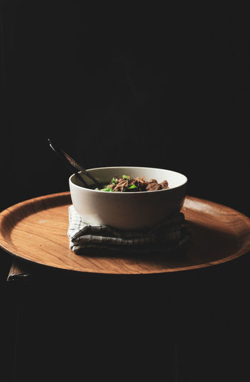 Close-up of soup in bowl on table against black background