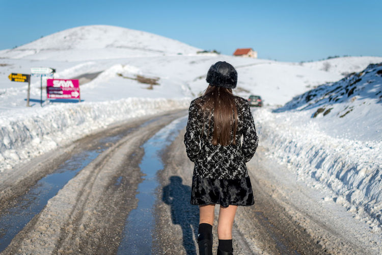 Rear View Winter Snow One Person Cold Temperature Nature Day Road Real People Transportation Clothing Full Length Lifestyles Land Walking Leisure Activity Warm Clothing Women Outdoors Snowcapped Mountain