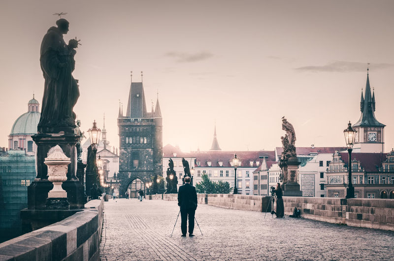 Rear View Of Man With Walking Cane On Charles Bridge Against Sky