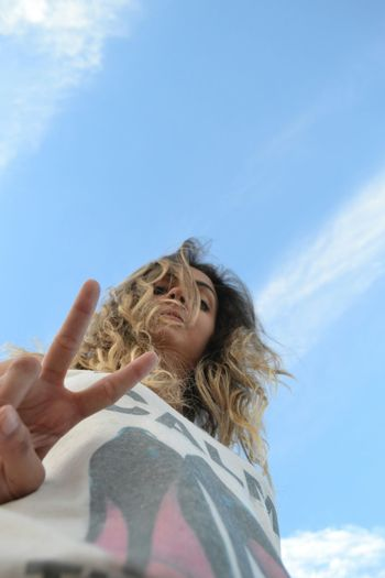 Low angle portrait of young woman showing peace sign while standing against blue sky