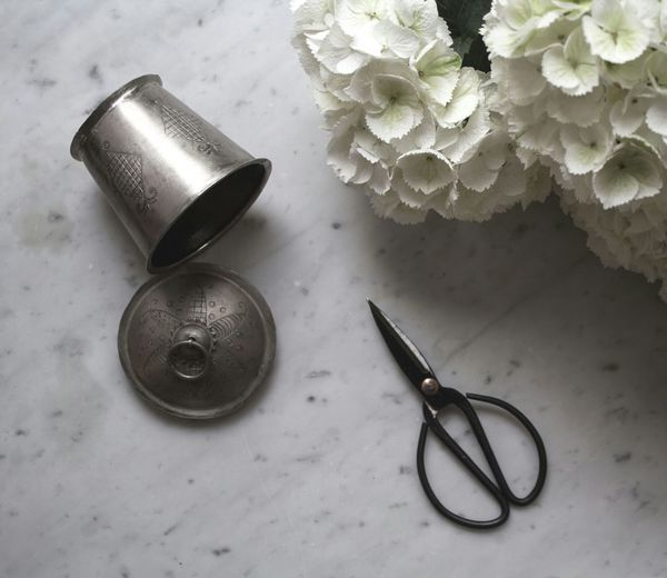 High angle view of scissor by white flower and metal container on floor