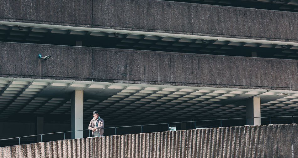 Man standing in car park with strong brutal architecture Architecture Boy Building Exterior Built Structure Carpark Day Fashion Framed Grey Leading Lines Man Outdoors Rail Real People Street Urban Urban Landscape Colour Your Horizn