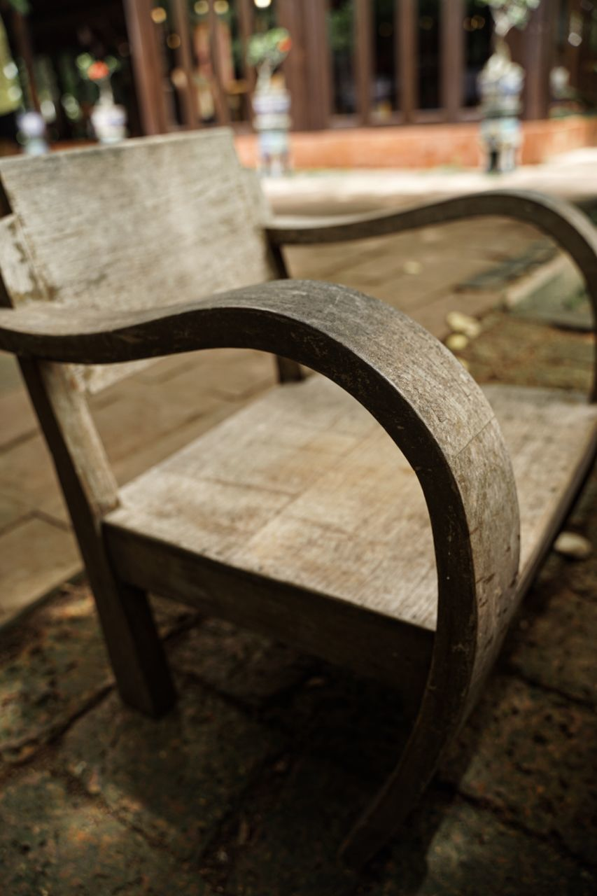 seat, chair, focus on foreground, table, absence, no people, wood - material, empty, close-up, building, architecture, day, selective focus, outdoors, footpath, street, built structure, sidewalk cafe, city, wheel
