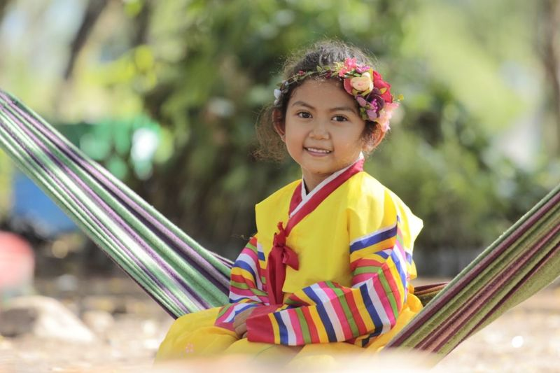 Portrait of cute girl smiling while sitting on hammock