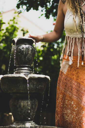 Midsection of woman by drinking fountain against blurred background