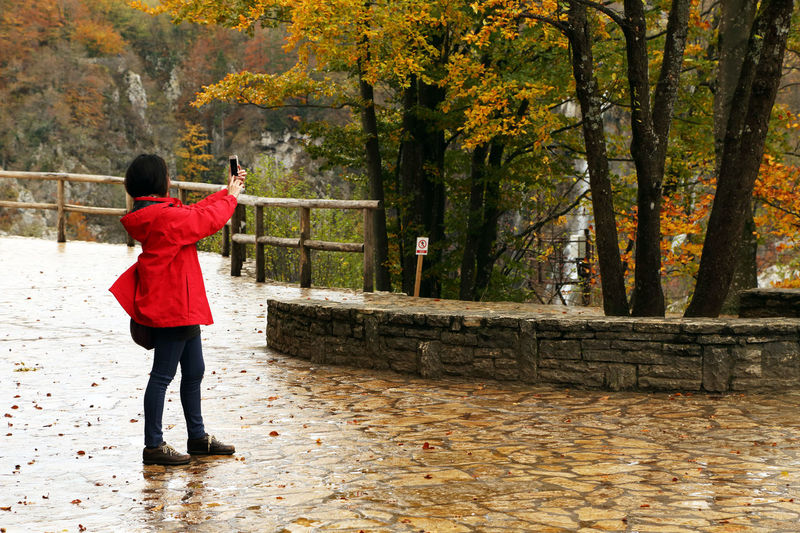 Woman photographing autumn trees while standing at plitvice lakes national park
