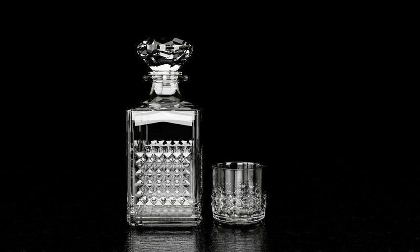 Close-up of glass jar on table against black background