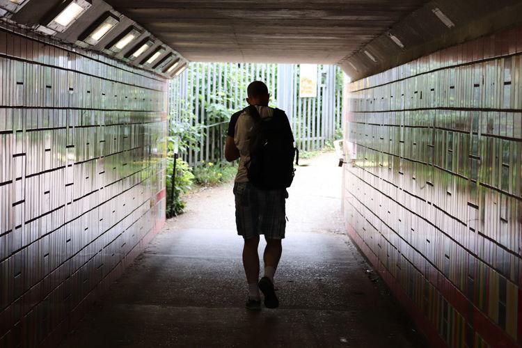 Full length rear view of man walking in underground walkway