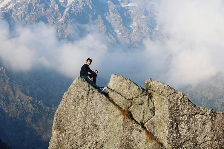 Full Length Of Man Sitting On Mountain At Mcleod Ganj