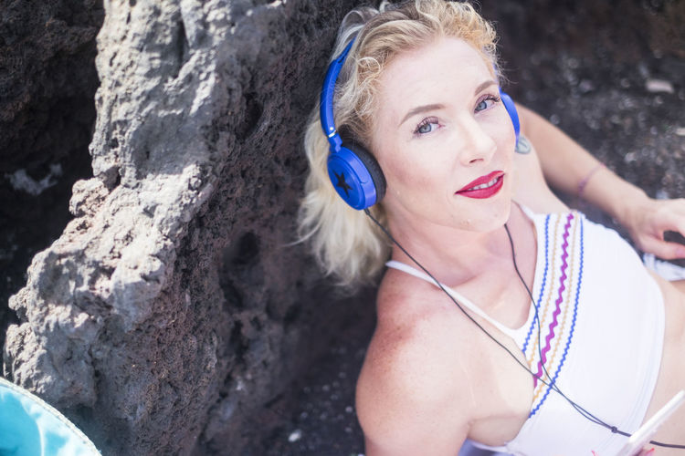 Pretty middle age young woman looking at smiling at the camera while listen music with blue headphones with star - red lipstick and blue eyes caucasian people enjoying the outdoor Leisure Activity Real People Women Portrait One Person Lifestyles Front View Young Adult Looking Young Women Beautiful Woman Beauty Emotion Looking At Camera Adult Day Focus On Foreground Headshot Outdoors Lipstick Relaxing Sunny Summer Blue Eyes Blue Blond Hair Headphones Looking At Camera Music Listening To Music Caucasian Rocks Beach Bikini