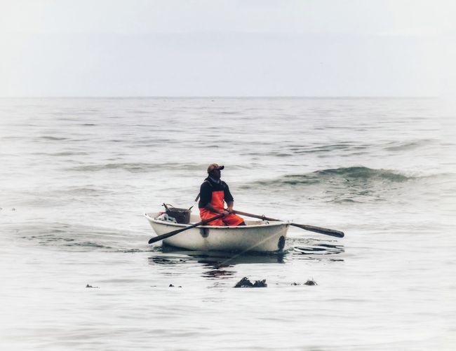 Man in boat on sea against sky