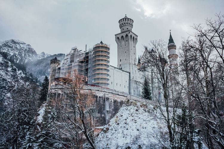 Hohenschwangau, Germany - November 17, 2017: Neuschwanstein Castle is a 19 century Romanesque Revival palace on a rugged hill above the village of Hohenschwangau. The palace was commissioned by Ludwig II. Construction works 2017. Cold Temperature Winter Snow Architecture Built Structure Building Exterior Tree Building Nature Plant Sky Bare Tree Place Of Worship Day No People Low Angle View Outdoors Office Building Exterior Skyscraper Culture Cultures Neuschwanstein Neuschwanstein Castle Schloss Castle