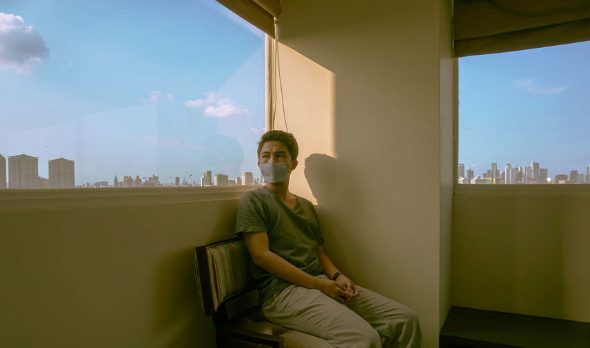 Man sitting by window against sky