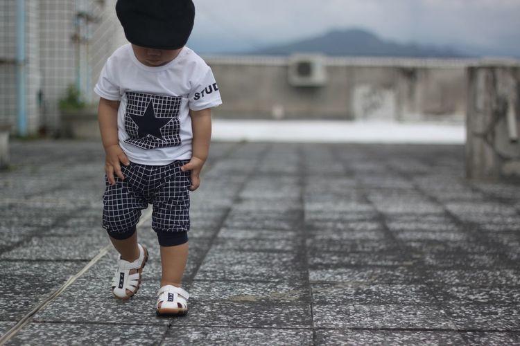 Full length of baby boy walking on street