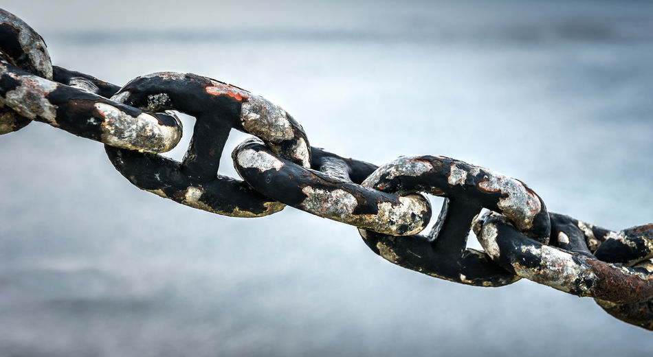 Close-up of rusty chain against sky
