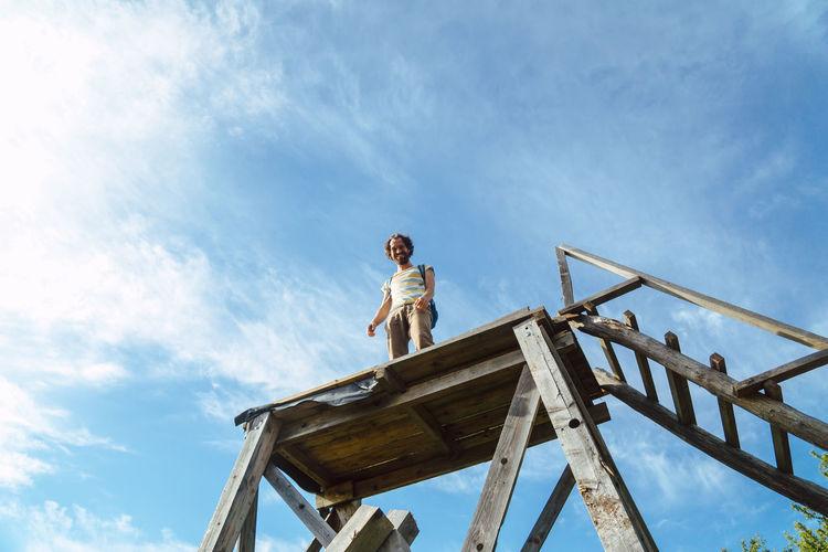 Man standing on ladder against sky