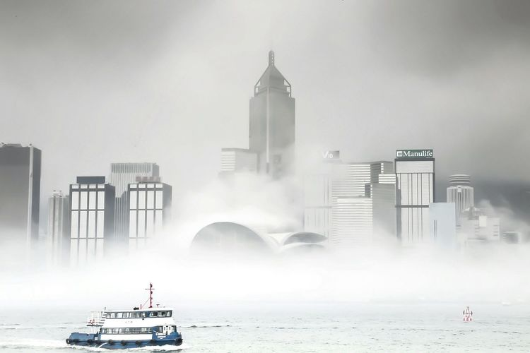 Ferry sailing in sea by city during foggy weather