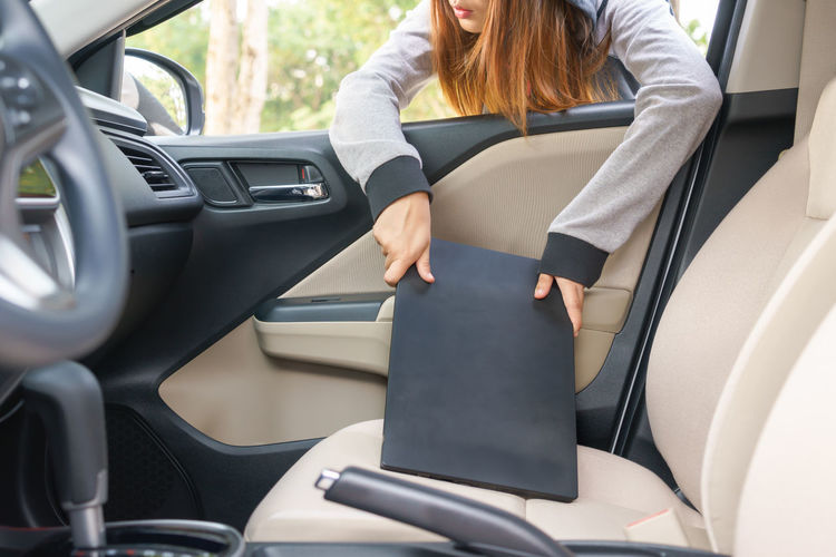 Woman holding laptop in car