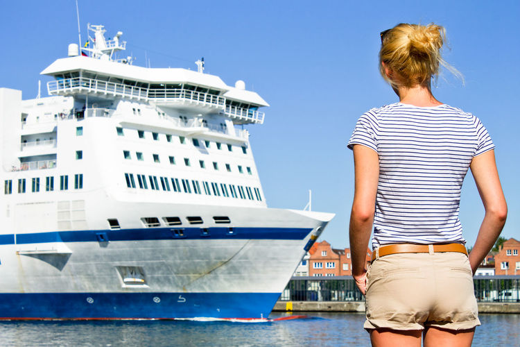 Rear view of woman standing at harbor against sky