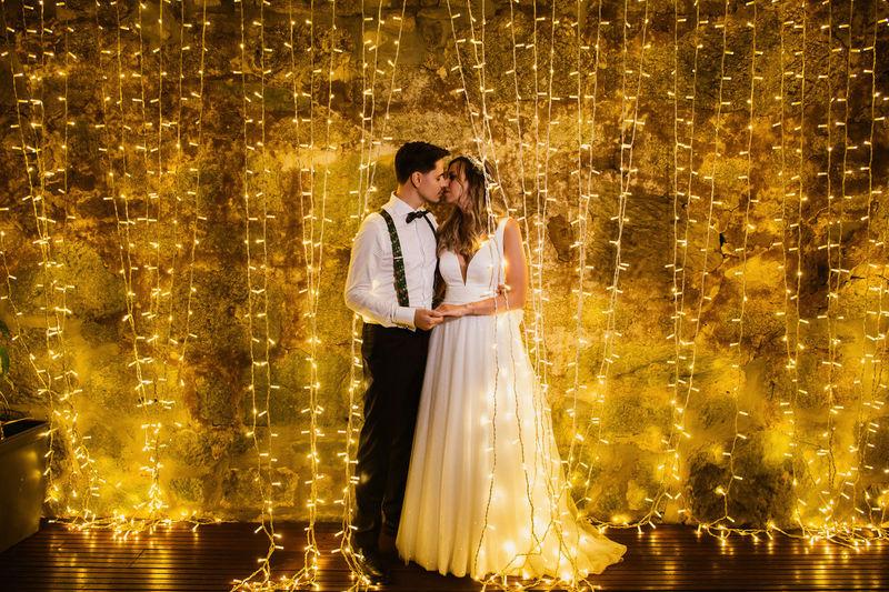 Full length of couple embracing against illuminated lighting