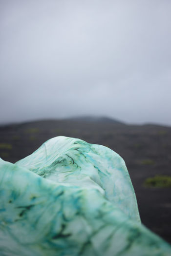 Close-up of green mountain against sky