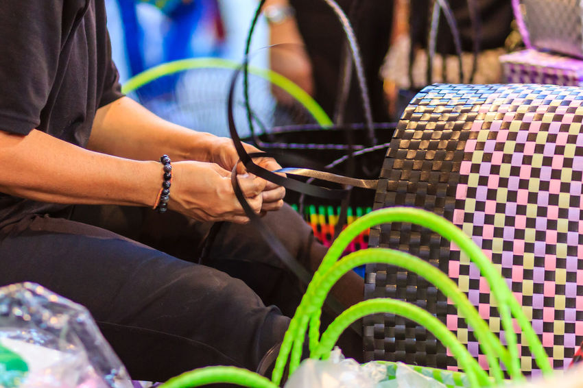 Close up hand of weaver during weaving basket made from plastic fiber. Weaver is weaving plastic basket show to the tourist in Bangkok, Thailand. Market Market Vendor Plastic Bag Weave Weaves Basket Basket Weave Close-up Day Human Hand Marketplace Midsection Multi Colored Outdoors People Plastic Plastic Baskets Real People Sitting Two People Weaver Weaving