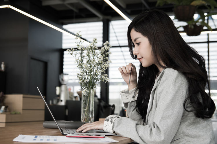 Side View Of Young Woman With Credit Card Using Laptop On Desk