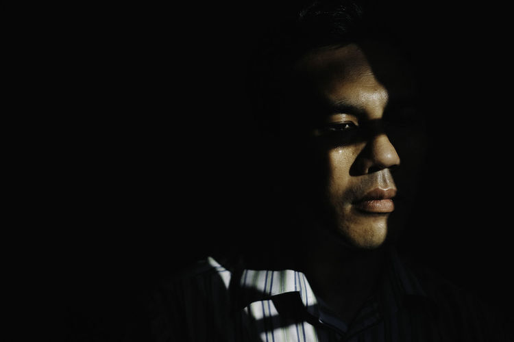Close-Up Of Young Man Against Black Background