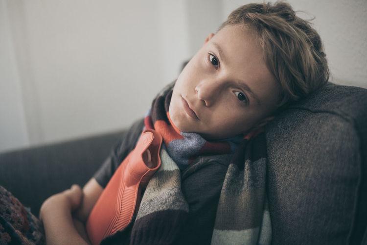 Portrait of sick boy sitting on sofa at home