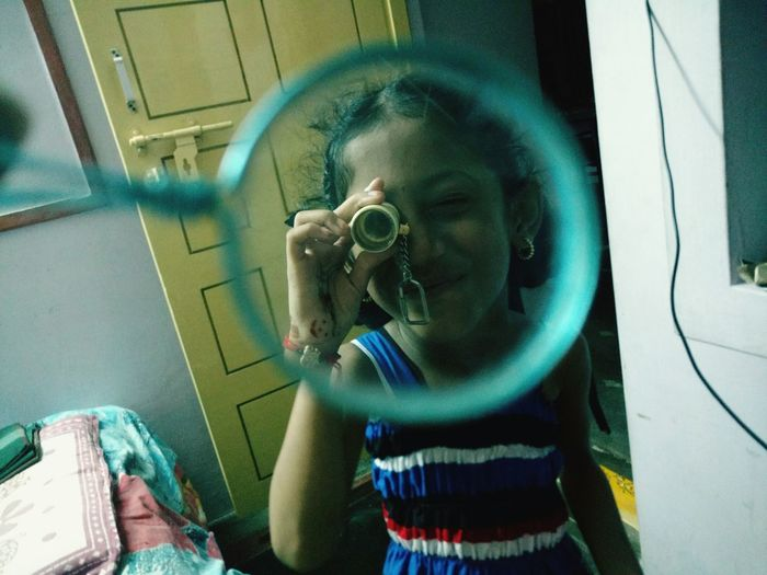 Close-up of girl seen from bubble wand looking through object at home