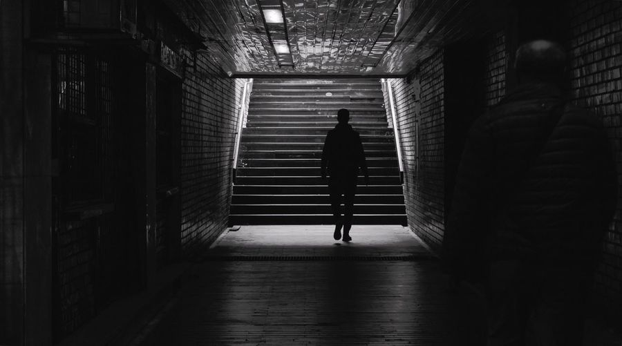 Rear view of man walking in underground walkway
