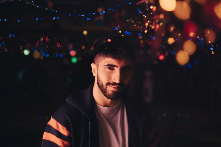 Portrait of young man against illuminated lights at night