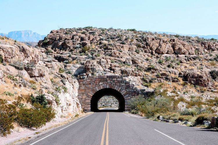 Empty road leading towards archway at big bend national park