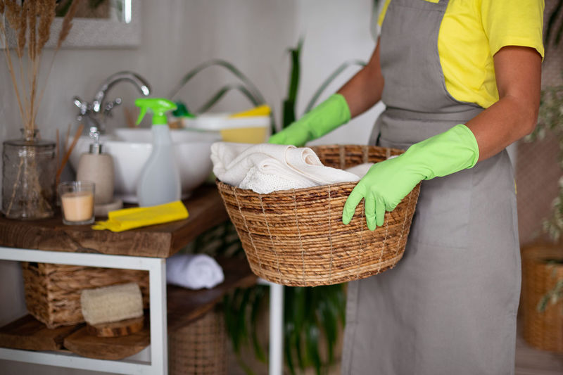 Midsection of man standing by basket at home
